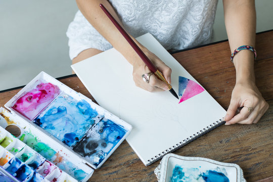 Latin artist painting with watercolor in her studio
