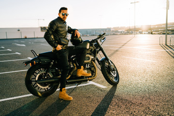 Attractive male with helmet leaning on modern motorbike on parking lot in city