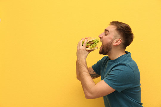 Young man eating tasty burger on color background. Space for text