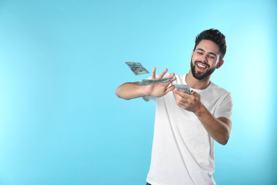 Happy young man throwing money on color background. Space for text