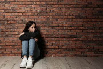 Upset teenage girl sitting on floor near wall. Space for text