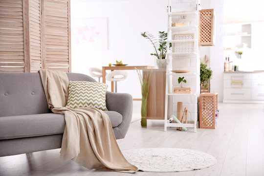 Modern eco style living room interior with wooden crates, shelves and sofa