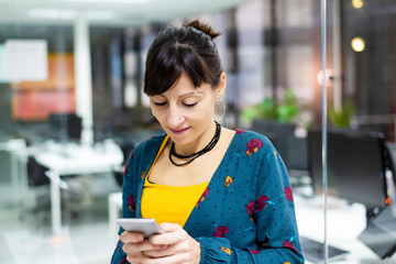 Lovely adult lady smiling and using smartphone while standing near glass wall in modern office