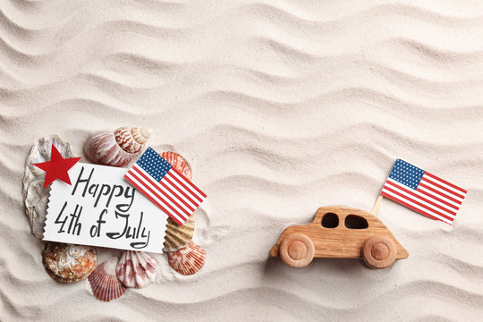 Flat lay composition with greeting card, USA flags and wooden car on sand. Happy Independence Day