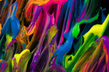 Closeup shot of spills of thick pigment of various colors mixing on black background
