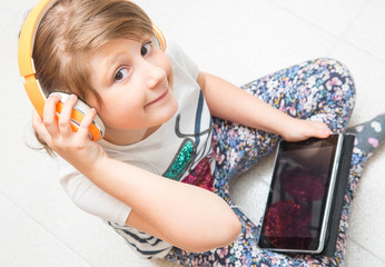 young child is listening music with headphone on tablet