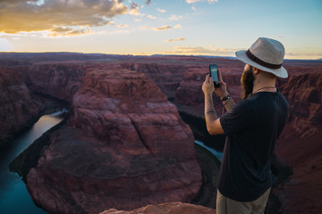Handsome bearded man in hat taking picture while standing against magnificent canyon and river during sunset on West Coast of USA