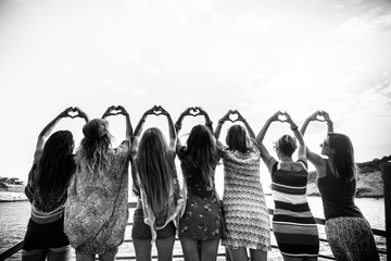 Rear view in black and white for romantic group of free females doing hearth sign with hands - women's day concept for love and freedom independence equality concept