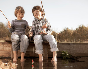 Happy boys go fishing on the river, Two children of the fisher with a fishing rod on the shore of lake