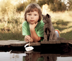 boy and his beloved kitten playing with a boat from pier in pond summer evening