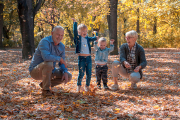 Grandchildren and grandparents throwing leaves in park and spending time together