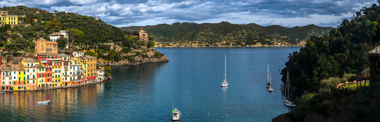 Colorful buildings in the raw, sailboats on sea and panoramic scenic view of village Portofino in Liguria region in Italy