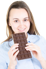 Beautiful woman smiling eating chocolate bar in isolated white background