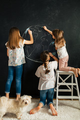 Young girl drawing planet earth on a blackboard
