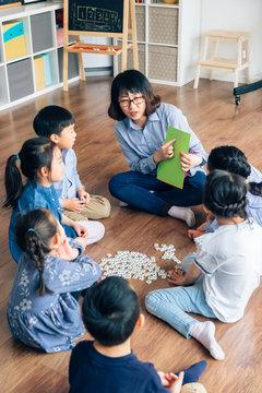 Teacher and preschool kids learning  in classroom