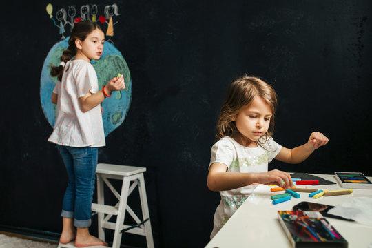 Girls drawing planet earth on blackboard