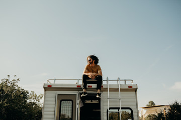 guy sitting on top of a camper trailer