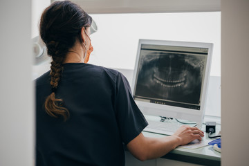 Orthodontist in the dental clinic showing an x-ray on the comput