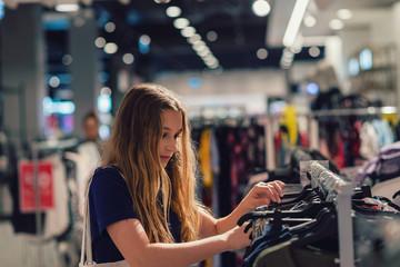 teen girl browsing through clothing rack