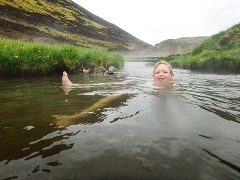 Blond boy having fun swimming in Iceland hot river