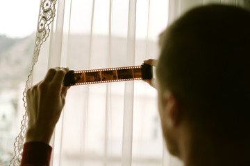 Young man looking at the film roll