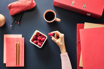 Container with raspberries and cup of coffee on black desk with