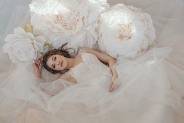 From above portrait of young attractive woman in wedding dress posing with big artificial white flowers