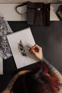 Crop woman creating tattoo sketch