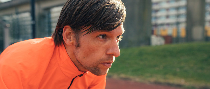 Close up of a male runner or athlete looking at the running trac