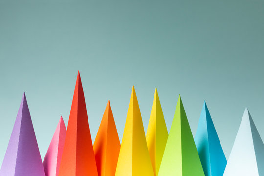 Rainbow pyramid shapes arranged on a bright blue background. (3)