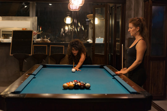 Girl friends playing pool in a bar