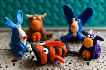 Animals (rabbits, cows and fish) from multi-colored plasticine, which hardens. Children's creativity. Funny clay toys.