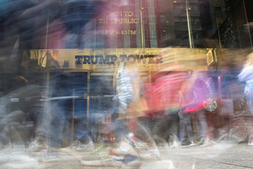 Pedestrians walk past and take pictures in front of the Trump Tower on 5th Avenue in the Manhattan borough of New York