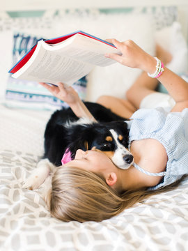 Young girl reading on her bed