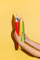 Hand holding a pencils in yellow background.