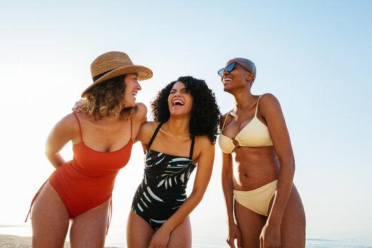 Group of smiling female friends enjoying beach