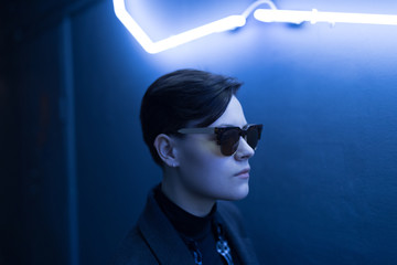 Portrait of short-haired woman with sunglasses under neon light