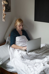 Woman is working on a laptop in her bed