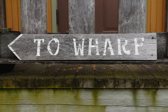 """direction sign with words """"to wharf"""" on rustic weathered grey wood board"""