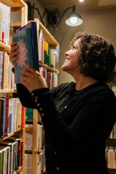 Female bookseller placing books on the bookshelf