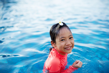 Cute asian little girl playing in the pool