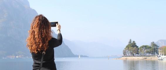 Turista al lago - scattare fotografie con lo smartphone