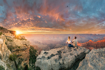 Man and woman sit on the edge of rim talking about future and watching the Grand Canyon sunset