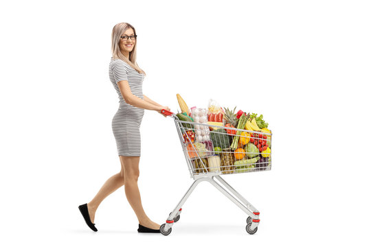 Full length shot of a young attractive woman pushing a shopping cart with food products and smiling at the camera