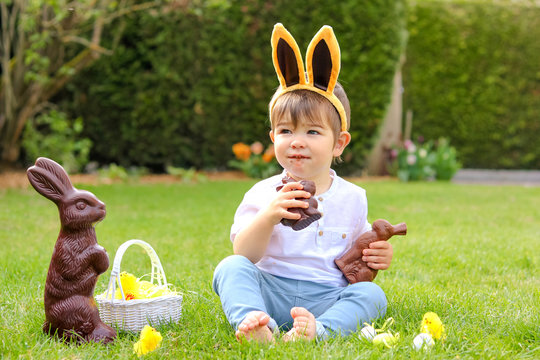 Cute little baby boy with bunny ears eating chocolate Easter bunnies sitting on green grass outside in the spring garden with basket of easter eggs and big chocolate rabbit. Happy sweet childhood