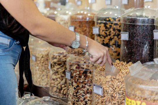 Woman's hand choosing walnuts in supermarket. Buying nuts sold in bulk.