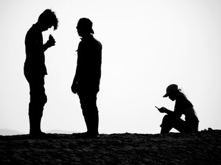 Silhouette of a small group of young adults on a beach: Two men stand together and a woman is sitting looking at her cellphone.