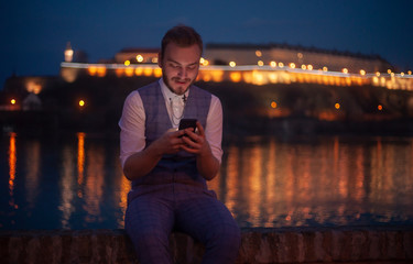 one young businessman sitting near a river while looking to his phone.