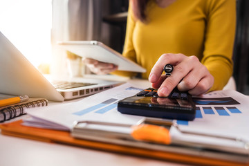 Business  women using calculator with computer laptop, Business accounting, budget and loan paper in office.