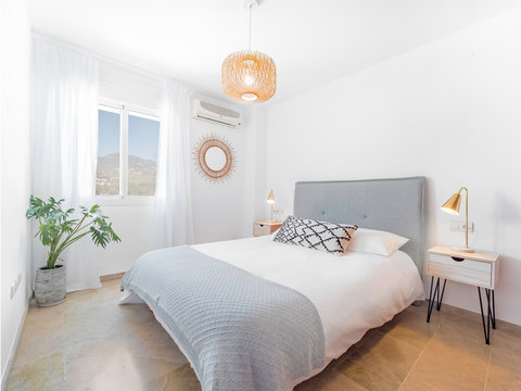 Comfortable hotel bedroom with felt headboard with natural fabric cushion, rattan lamp, wood nightstand and a big wooed wardrove.Holiday destination apartment with scandinavian style.